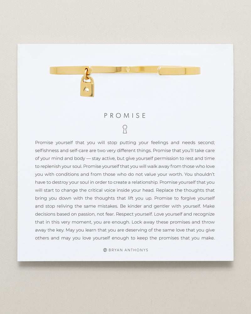 Bryan Anthonys Promise Gold Charm Cuff with a lock charm and crystal on card