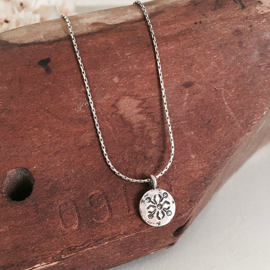 Silver pendant with tribal stamp hanging from sterling silver chain