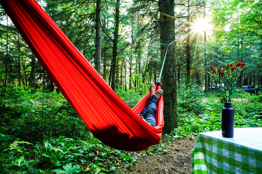 A woman lays in a red hammock with a hot drink in her hand