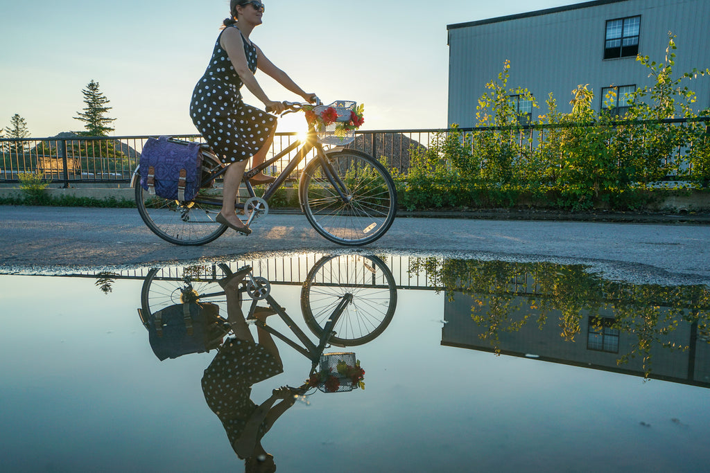Woman riding a bike by a puddle in the city on a sunny day