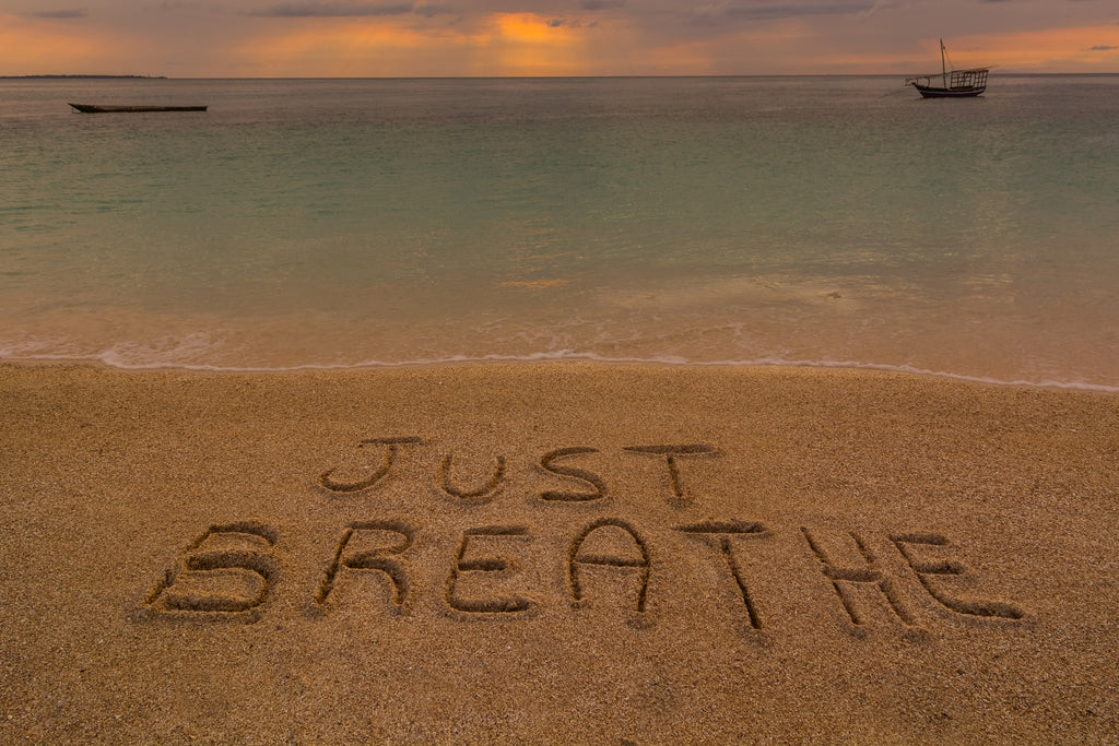 The words 'Just Breathe' written in the sand on the beach at sunset