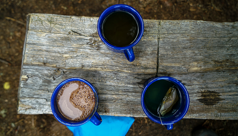 A overhead picture of three mugs on a bench outside