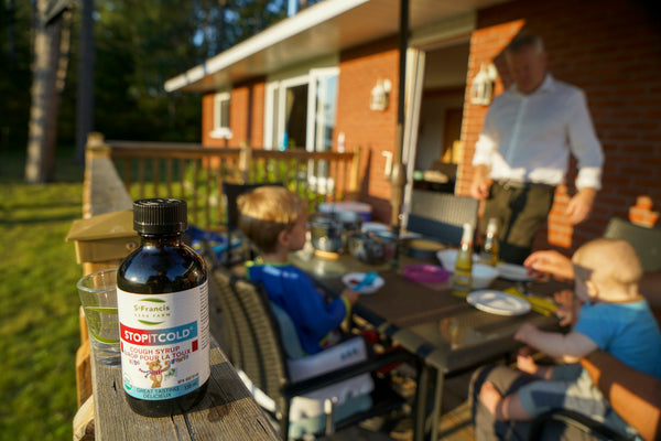 A bottle of children's Stop It Cold® Cough Syrup stands on a banister in front of a table outside on a porch