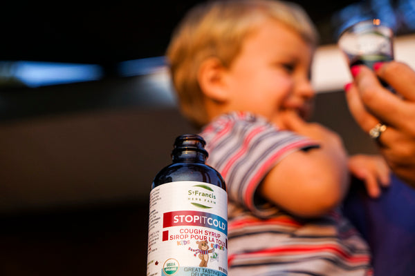 An opened bottle of children's Stop It Cold® Cough Syrup sits in front of a woman holding a child