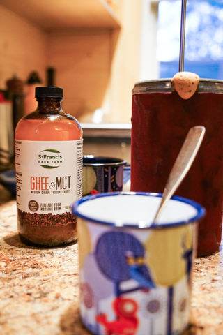 Picture of Ghee & MCT oil bottle on a counter beside a french press and coffee cup