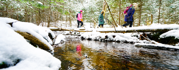 Three people walk along a running stream in the woods after snow has covered the ground.