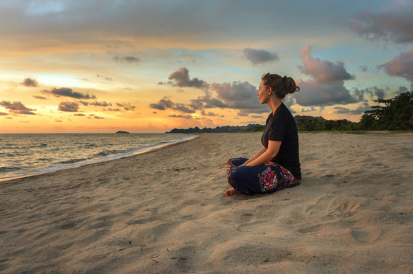 Woman sitting on sandy beach at sunset with waves lapping up on the sand