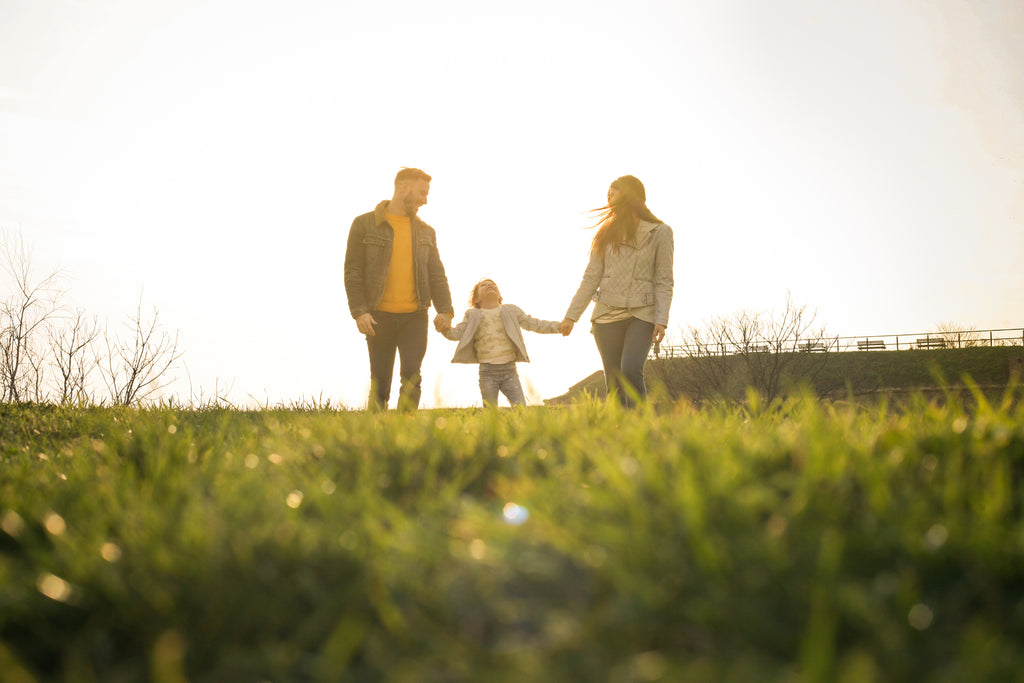 Family of Man, woman and little girl walking through the grass on a sunny spring day