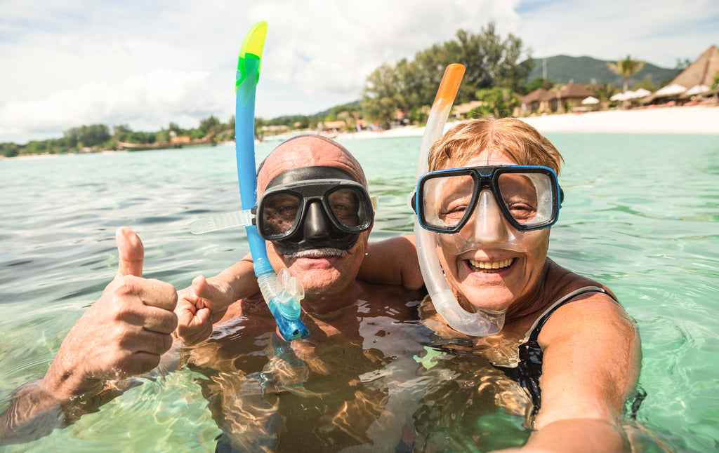 An older couple snorkelling in ocean waters with resorts in the background and a sunny day