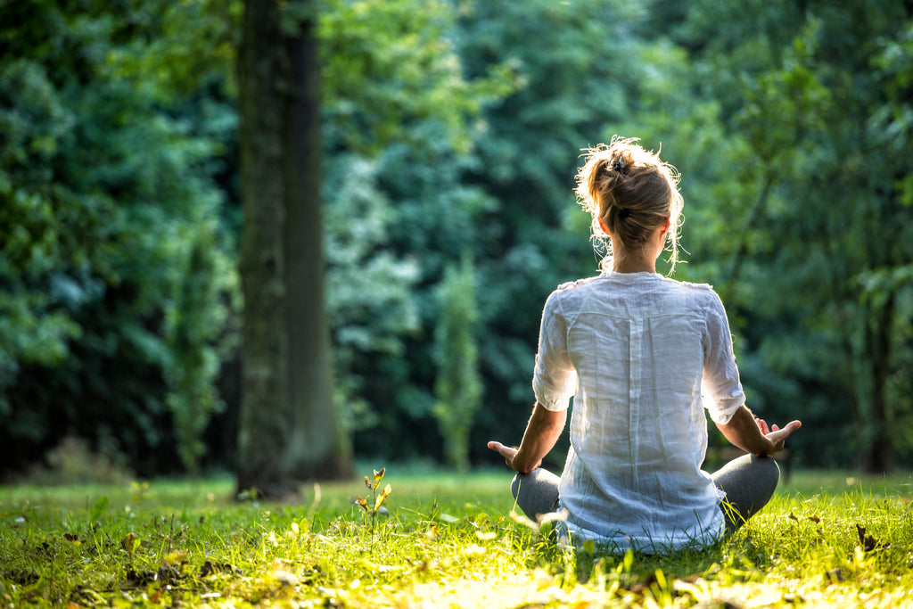 Picture of woman sitting grass in front of woods meditating