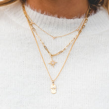 woman wearing An effortless-chic dog tag and star charm necklace.