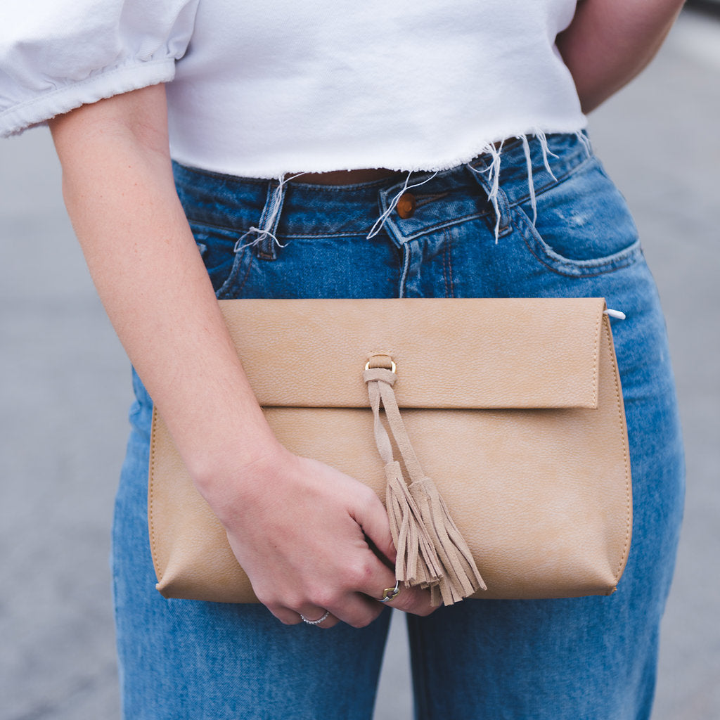 woman holding tan clutch features suede tassels and detachable chain . Made by Street level. Tan clutch, crossbody