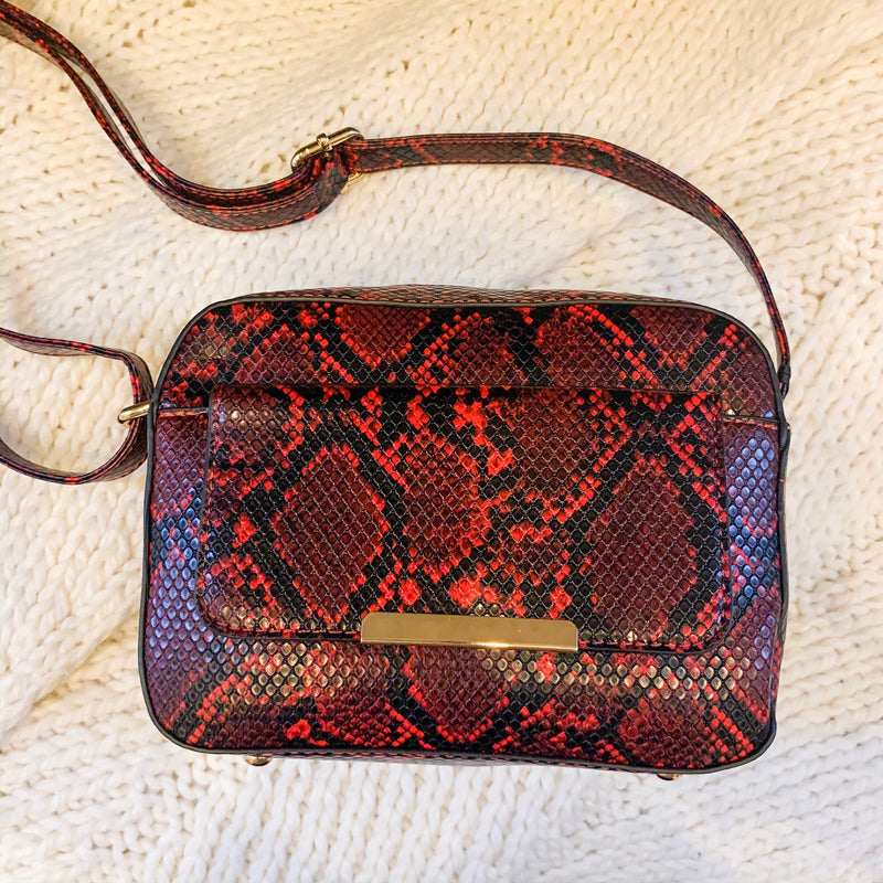 Get your snake print fix on with this trendy shoulder bag. This bag features an adjustable strap, front pocket with snap closure and back zipper pocket.   Interior space: medium