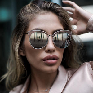 girl wearing round reflective lenses set in an understated metal frame with winged cat-eye arches