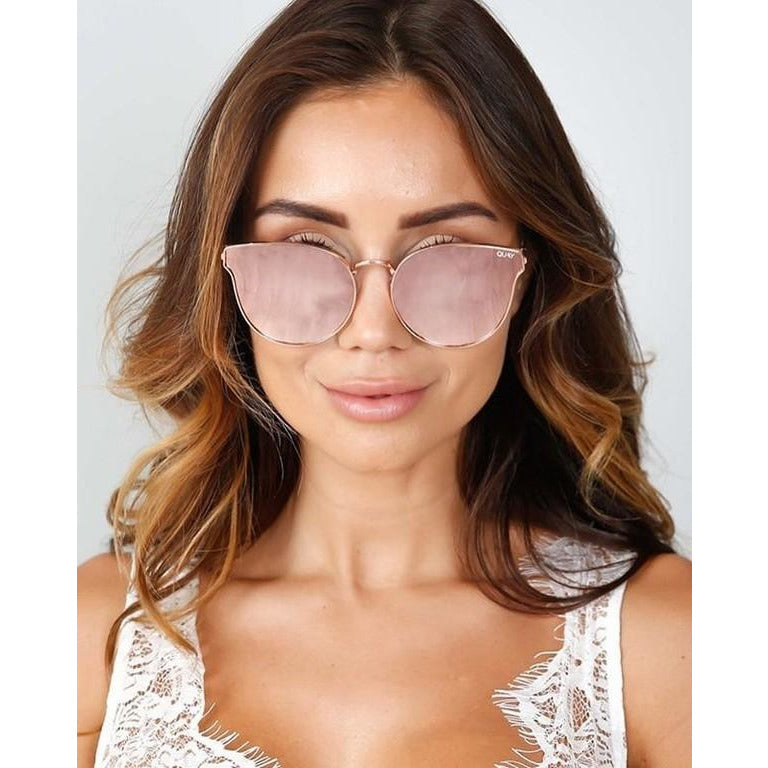 Girl wearing feminine pink cat eye sunglasses from Quay. Trendy pink sunglasses. Summer trend, spring 2019. Coachella, music festival