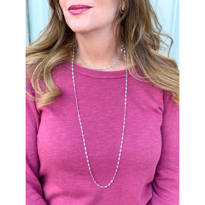 "girl wearing pink shirt and cubic zirconia simulated diamonds in silver/ rhodium. layer necklace. long necklace. Measures 18"" long. OMG Blings"