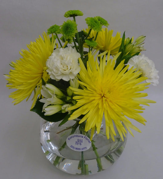 White and yellow and green flowers in a fishbowl glass vase