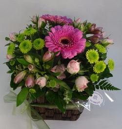 Spray roses, gerberas and green button chrysanthemums flowers in a basket