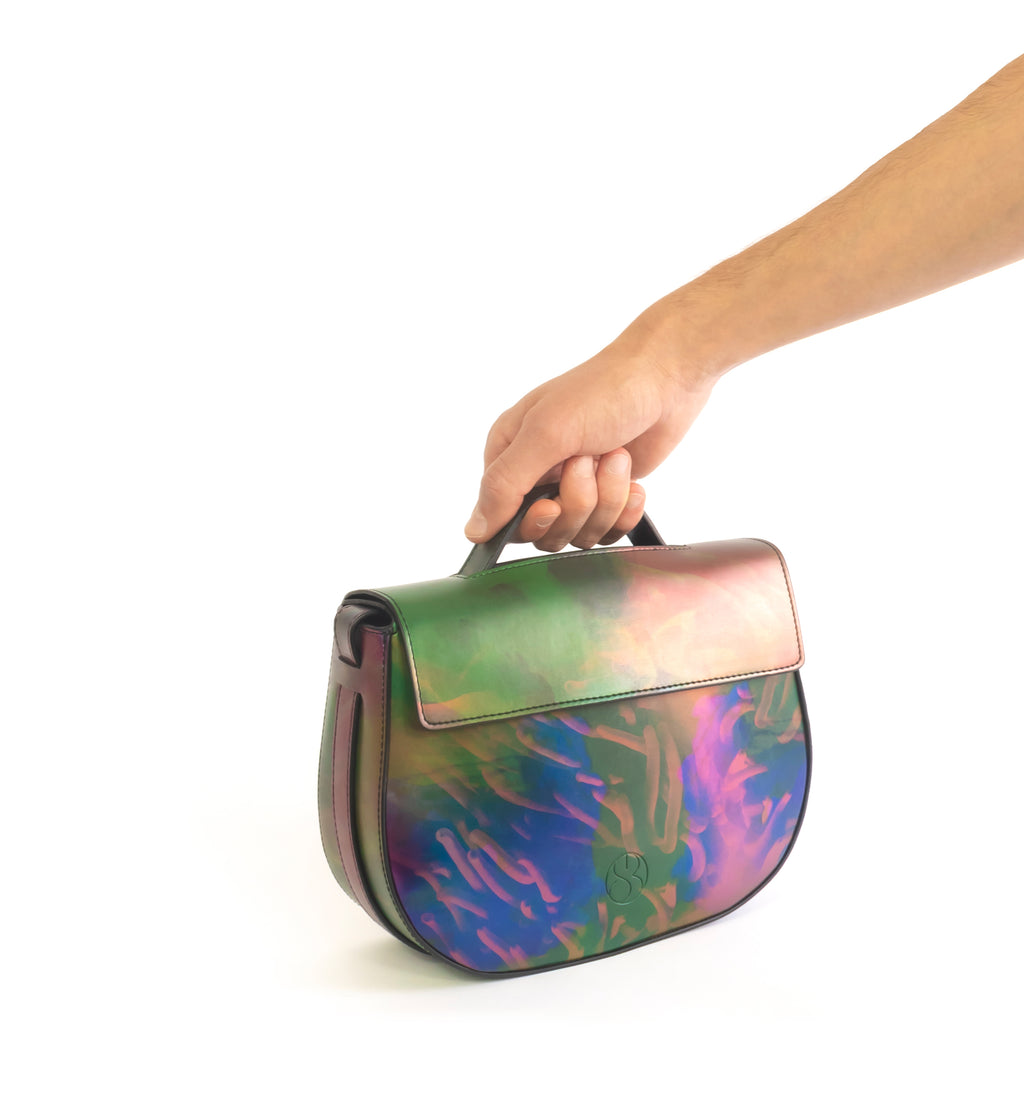 Printed iridescent vegan leather crossbody bag by Sydney Brown. Timeless, classic and modern. Hand view