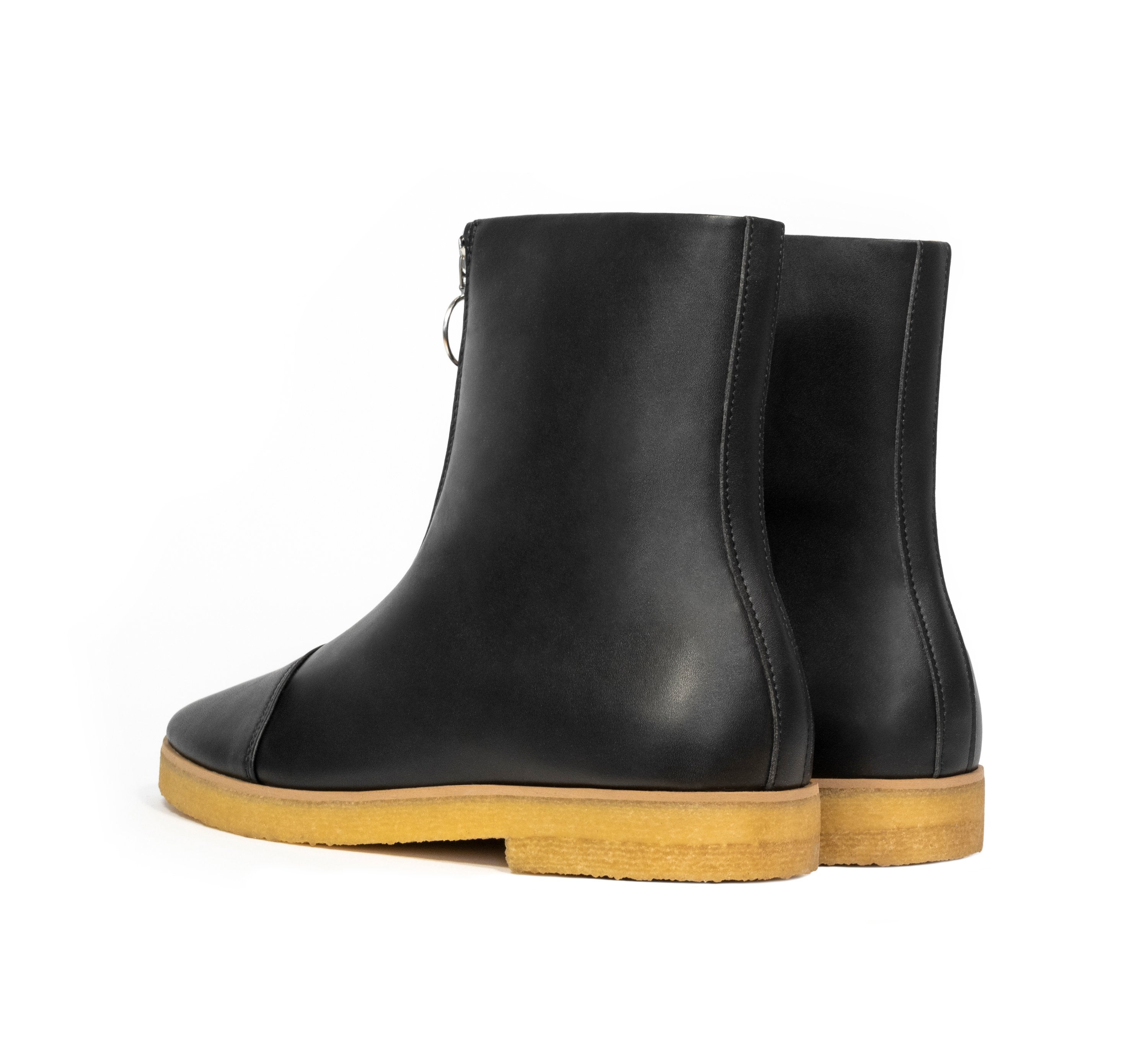 Black vegan leather boot with frontal zip, almond toe, natural rubber crepe sole.