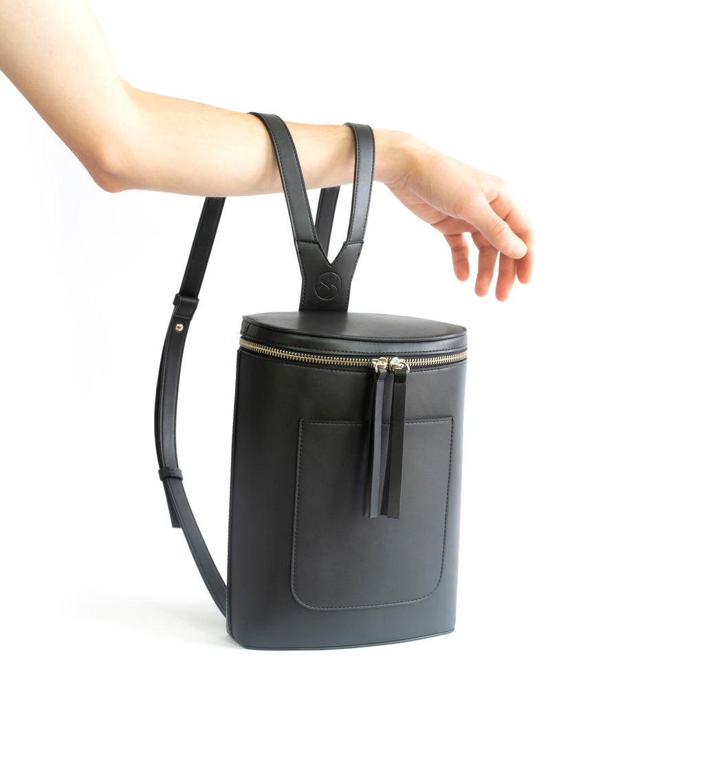 Black eco vegan leather bucket backpack by Sydney Brown. Timeless, classic and modern. Hand view