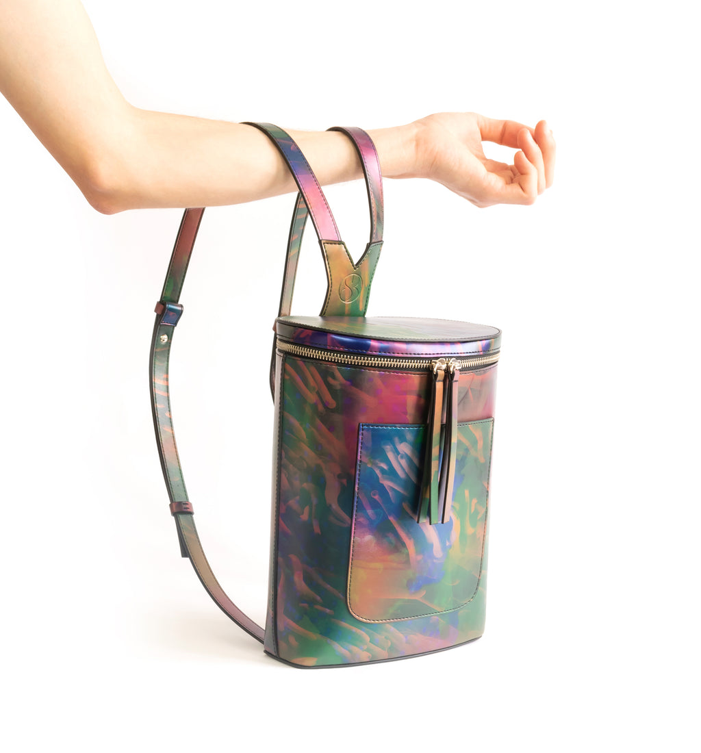 Printed iridescent vegan leather bucket backpack by Sydney Brown. Timeless, classic and modern. Hand View