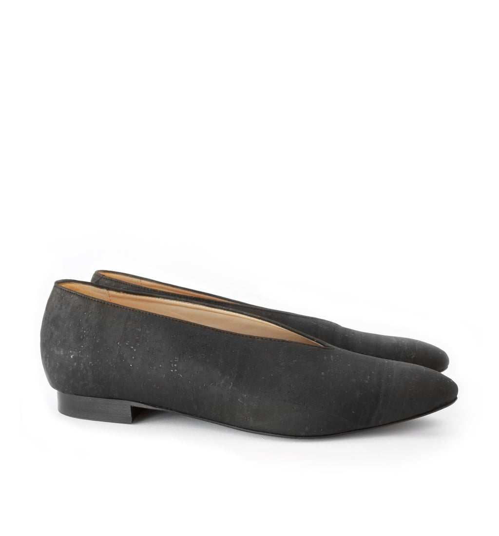 Flat with pointy toe in black matte cork, black sole with low wood heel.