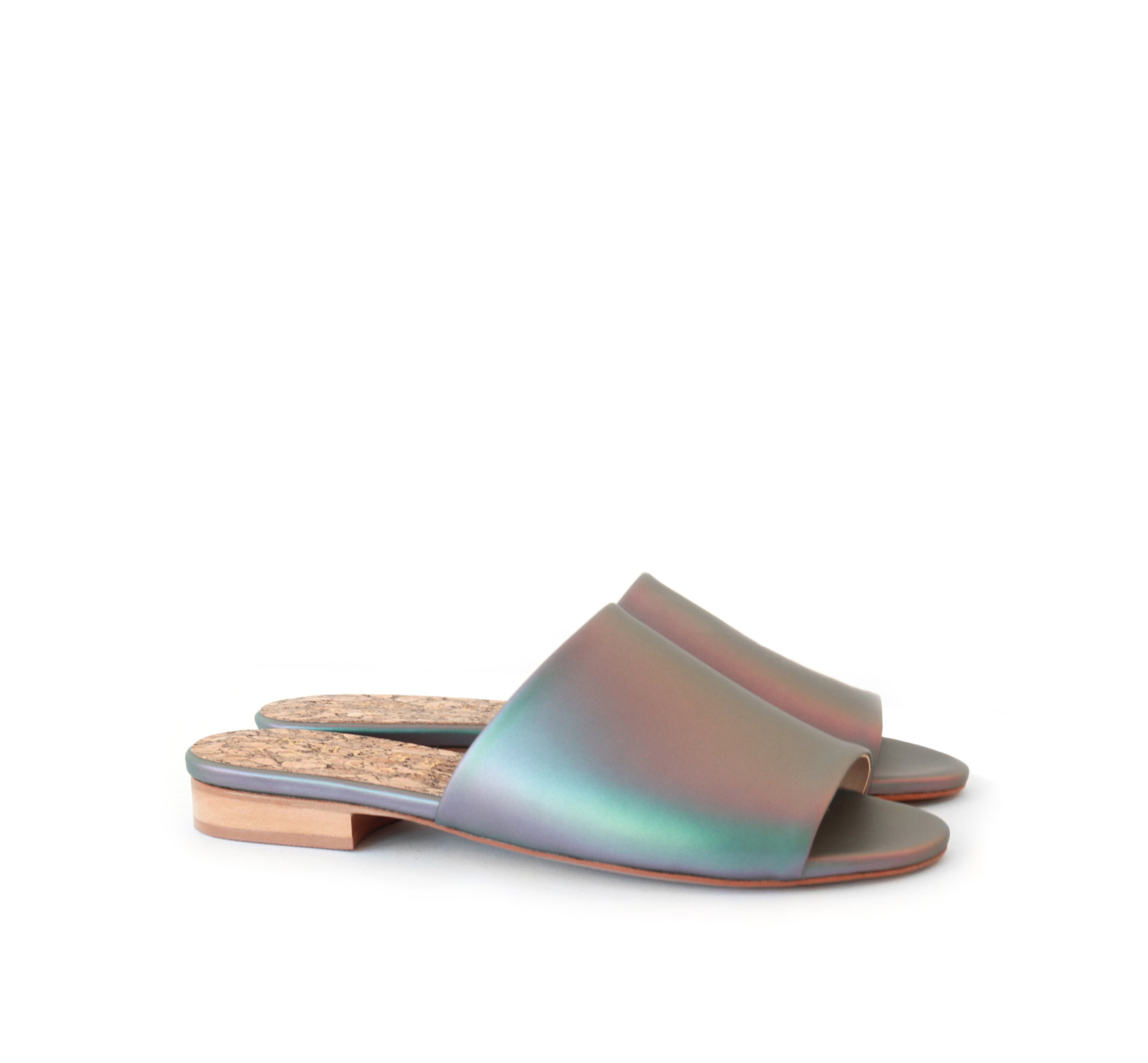Flat slides in iridescent vegan leather, small wood heel.