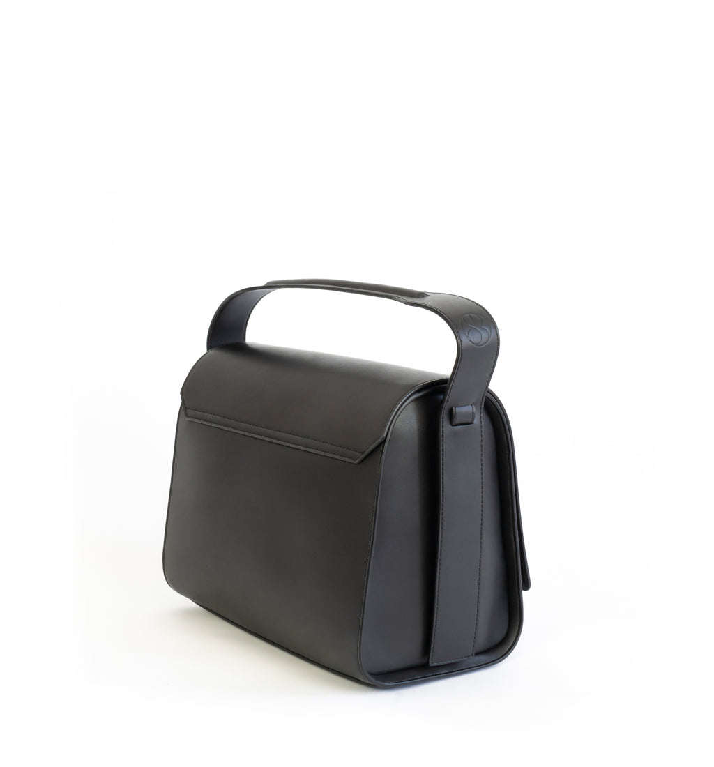 Black eco vegan leather barrel shoulder bag by Sydney Brown. Timeless, classic and modern. Angle back