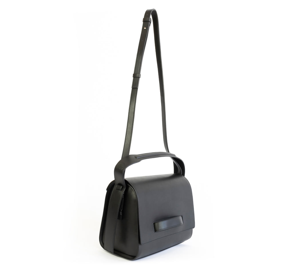 Black eco vegan leather barrel shoulder bag by Sydney Brown. Timeless, classic and modern. Angle Front view shoulder strap