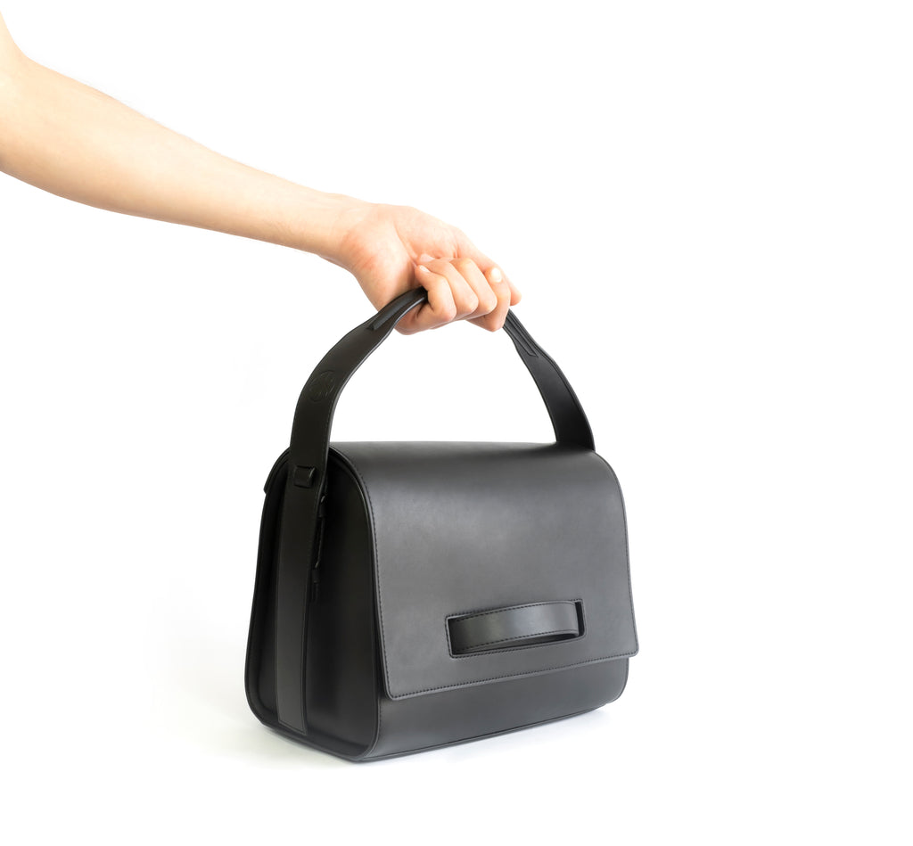 Black eco vegan leather barrel shoulder bag by Sydney Brown. Timeless, classic and modern. Hand view.