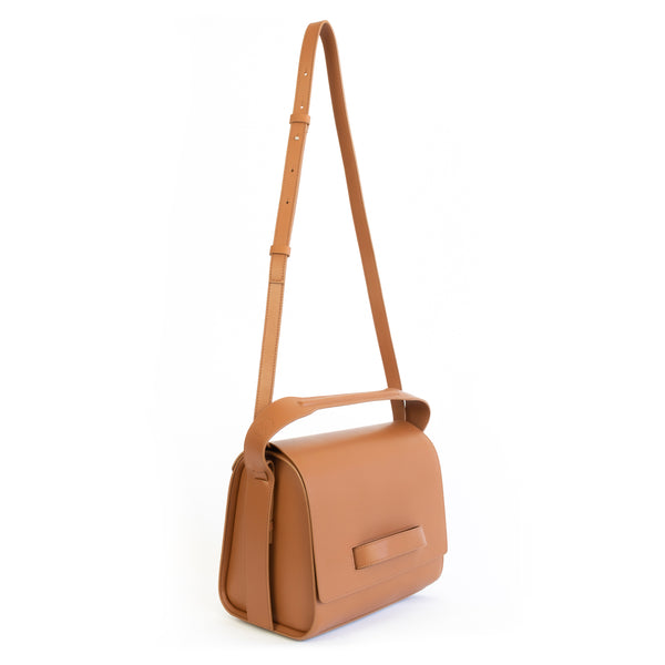 Brown eco vegan leather barrel shoulder bag by Sydney Brown. Timeless, classic and modern. Angle front view shoulder strap