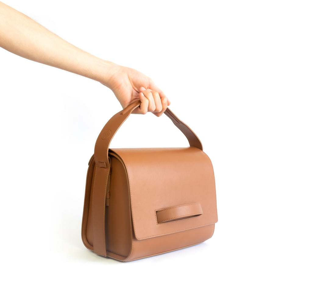 Brown eco vegan leather barrel shoulder bag by Sydney Brown. Timeless, classic and modern. Hand view.