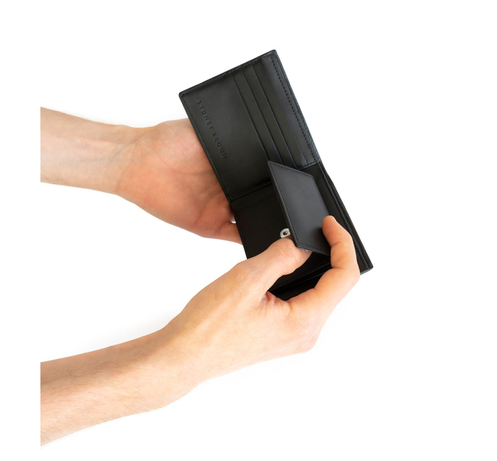 Unisex bifold wallet, practical and timeless. Black Emboss faux-leather. Hand view.