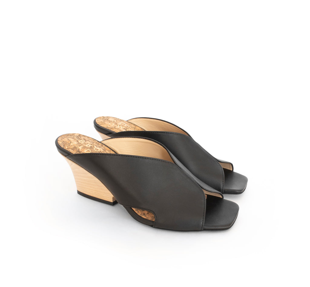 Black faux-leather mule slide with a curved design high heel in light brown wood.