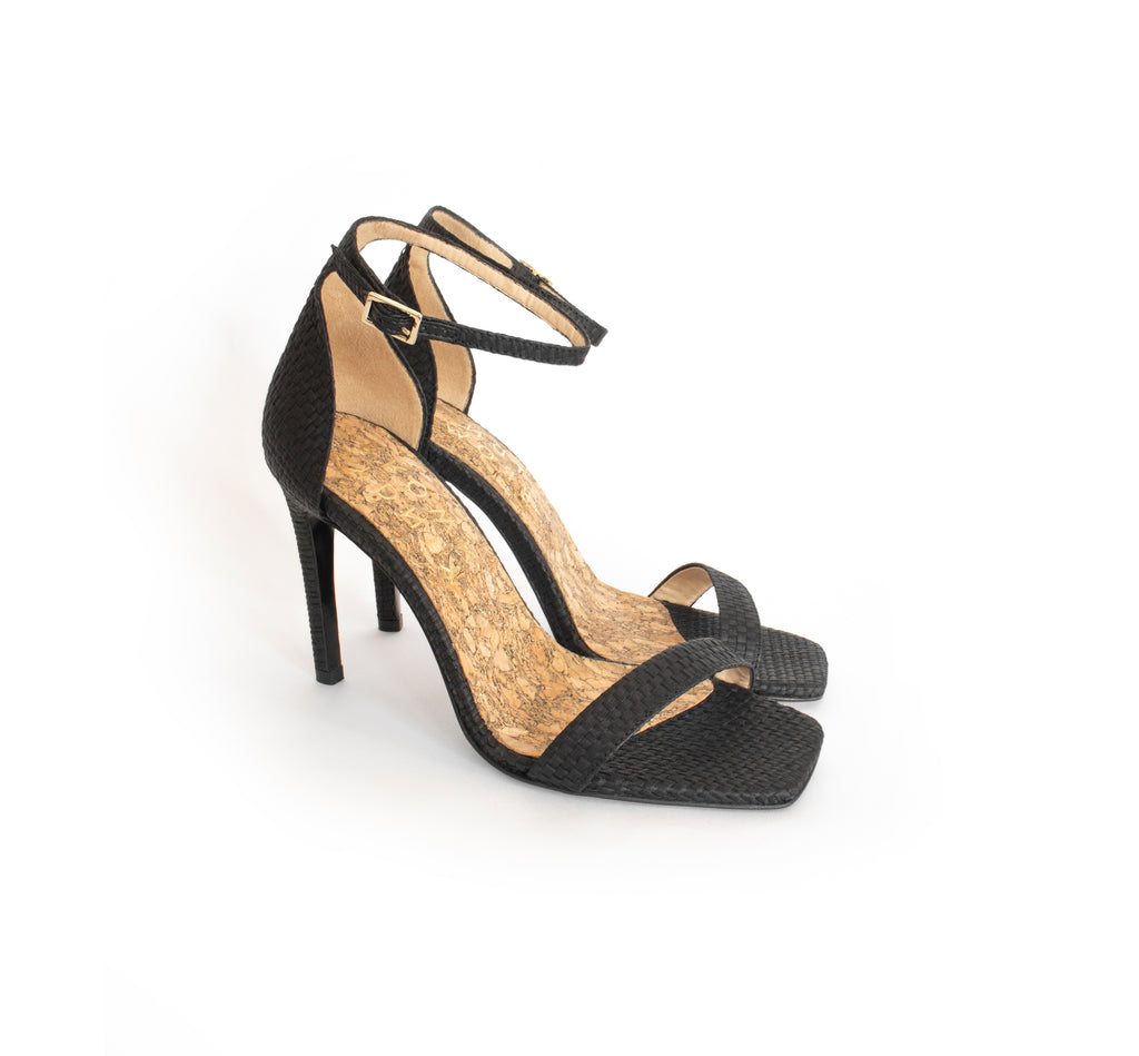 High stilettos in black raffia, ankle strap with metal buckle, with a recycled wood pulp stiletto heel, covered in black raffia.
