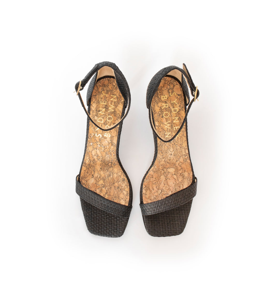 Low Stiletto in Black Raffia, ankle strap with metal buckle. Mid-heel in recycled wood pulp, covered with black raffia.