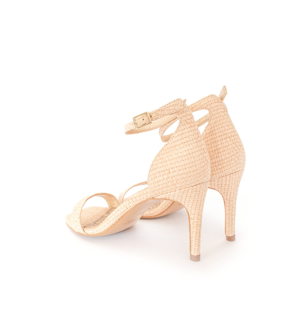 Low Stiletto in natural raffia, ankle strap with metal buckle. Mid-heel in recycled wood pulp, covered with natural raffia.
