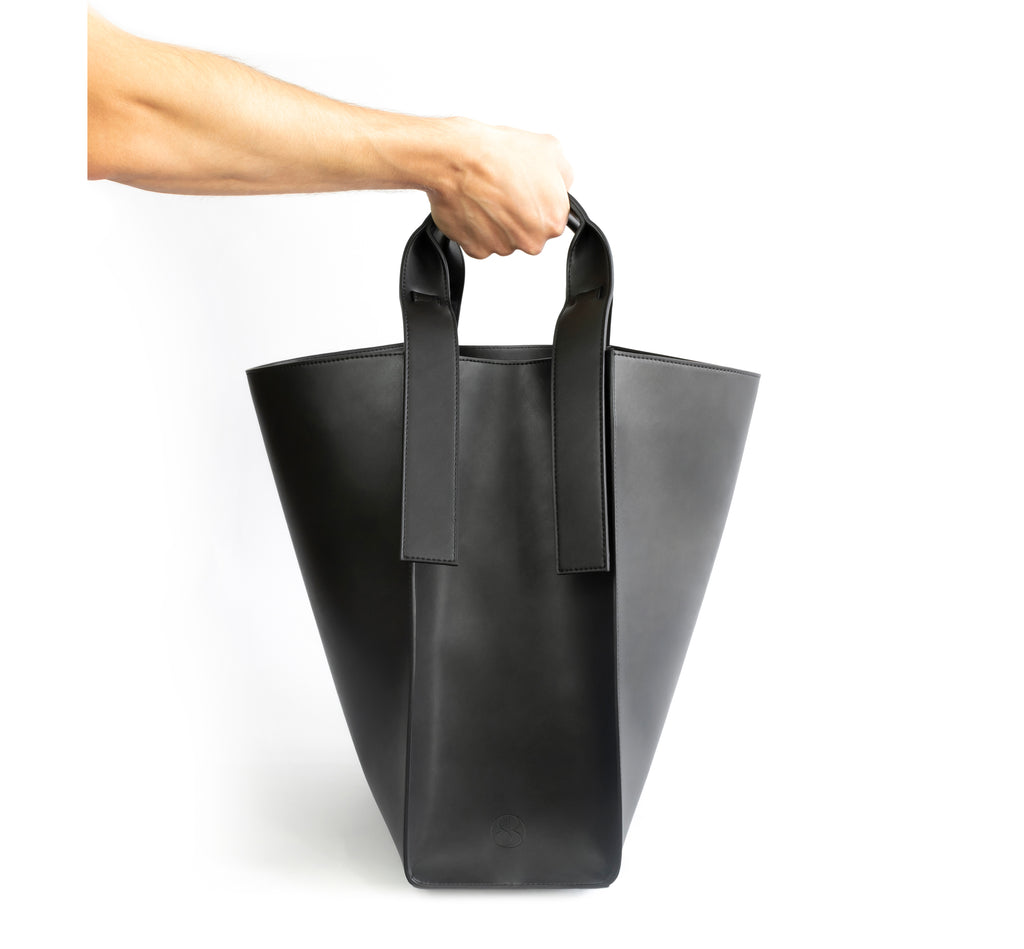 Black eco vegan leather tote shoulder bag by Sydney Brown. Timeless, classic and modern.  Hand view.