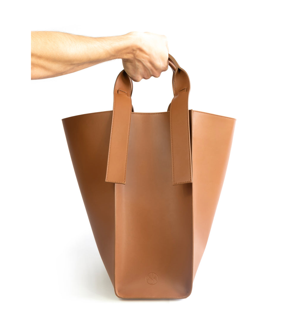Brown eco vegan leather tote shoulder bag by Sydney Brown. Timeless, classic and modern. Hand view.