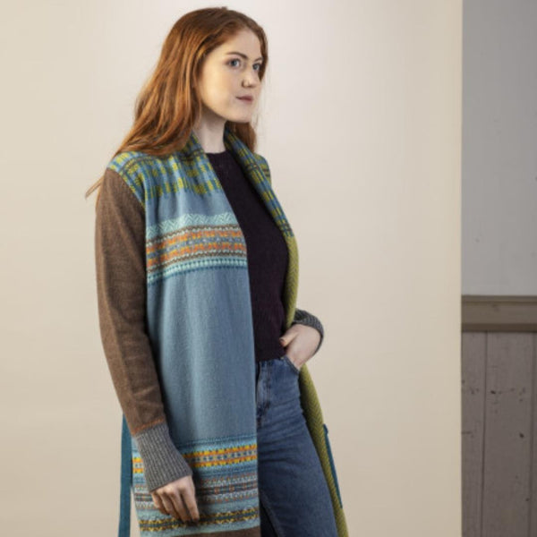 A redheaded woman models the Tumeric pioneer Longline Cardicoat. Features the right side which is a blue base with patterns in blue, orange, brown, yellow and grey.