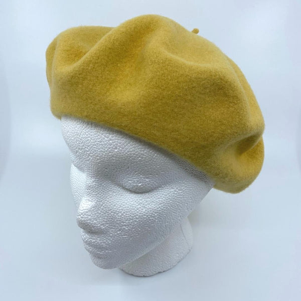 a goldenrod coloured tam/beret on a mannequin head