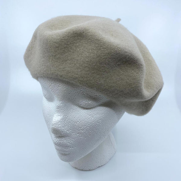 a light beige tam/beret on a mannequin head