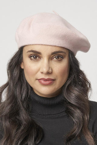 a brunette model wearing a light pink beret