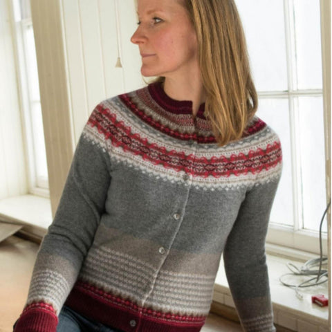 a woman sits near a bright window wearing a 'Greyberry' fairisle cardigan (colours are grey, red, white and burgundy)