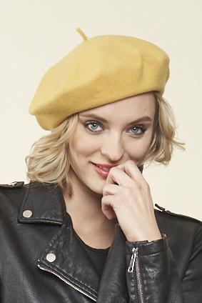 a blonde model wearing a leather jacket and a bright gold beret