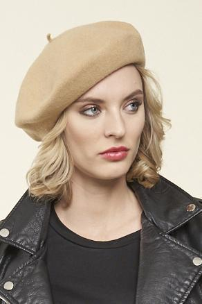a blonde model wearing a leather jacket and a sand coloured beret