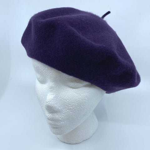 a dark purple tam/beret on a mannequin head
