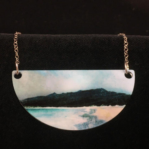 detail image of Reef Beach necklace  - a dark rocky outcrop silhouetted against blue and grey stormy skies