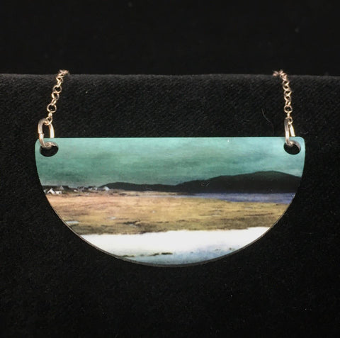 close up of the Salt Marshes necklace - dark mountains divide a yellow and white foreground from a blue-green sky